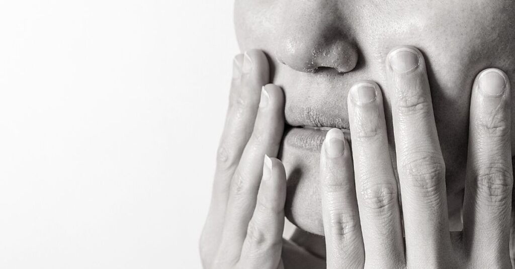 woman hold her mouth